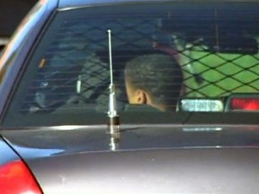 First to be apprehended, a young suspect sits in the back of a sheriff detective's car at the condo complex.