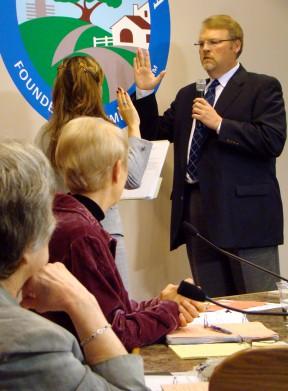 Councilwomen Marsha McLean, left, and Laurene Weste watch as Frank Ferry is sworn in as mayor in April 2012.
