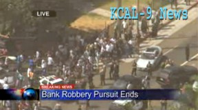 Crowd gathers in South L.A. as Canyon Country bank robbery suspects are apprehended following a chase.