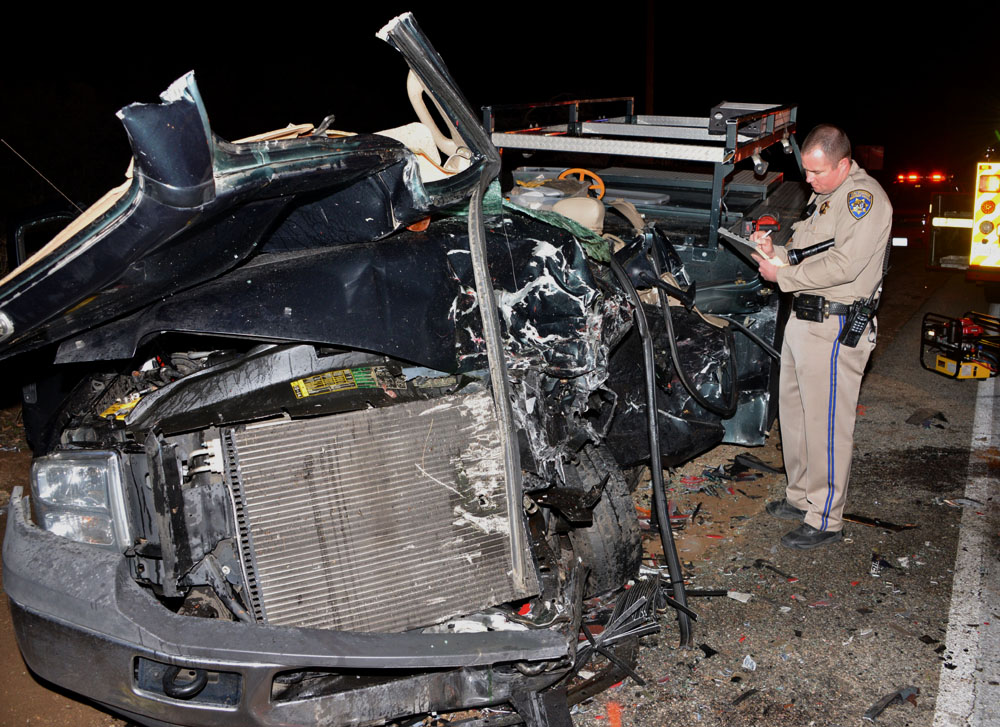 CHP officer investigates head-on collision on Sierra Highway in Canyon Country in which one person was killed Friday night. Photo by Rick McClure