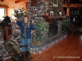 "Stacy Gunderson shows off one of Monte Montana's saddles in the living room of the ""horse house"" at Animal Tracks Inc."