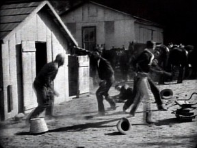 Fight scene in front of the chicken house (at left), which has a lean-to on its right (west) side; and the tin garage, which has a double-hung window on its left (east) side. The tin garage is long gone.