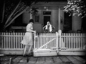 "Hazel Mills enters through the gate in the white picket fence in front of the Pico Cottage (aka Big House) while cameraman Hap Depew gives us a view of the front door and porch in this screenshot from ""The Last Roundup"" (1929)."