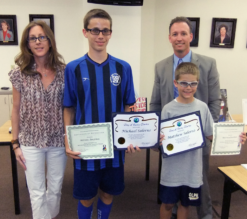 Michael Salerno's brothers accept the prize for the OLPH student's winning poem, from contest judge Kim Goldman of SCV Youth Project and Santa Clarita City Manager Ken Striplin.