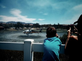 Boy watches a helicopter scoop water from a pond in the West Ranch community. Photo by Austin Dave/SCVNews.com.
