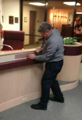 School board member Doug Bryce removes Winkler's name plate after the vote is taken.