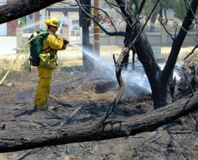 A firefighter douses a hot spot at the southwest intersection of Elizabeth Lake Road and Ranch Club Drive on Sunday.