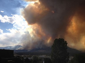 A large plume of smoke rises over Colorado Springs, Colo., that cast a wide, dark shadow over homes and businesses. Wildland fires burn intensely and creating a defensible space around your home can be the difference between a close call and complete destruction. (Adam Drake/Inciweb.org)