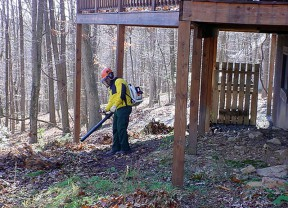 Don't forget to clean anything stored underneath decks and porches and remove vegetation as a precaution against wildland fires. Leaves, twigs and other debris act as fuels that feed a blaze. Keep leaves and needles off of your roof and deck and make a fuel-free area within 3-5 feet of your home's perimeter. (Photo used by permission from the National Fire Protection Association Firewise Communities Program)