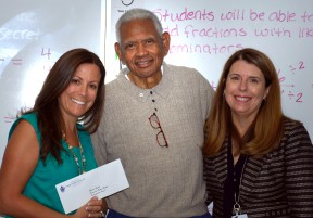 "Ed ""Papa Duck"" Bolden (center) presents a check for a $200 classroom grant to James Foster Elementary School teacher Shauna Booth (left) with principal Dr. Deborah Bohn in attendance. Mrs. Booth was the winning teacher in Samuel Dixon Family Health Centers' annual rubber ducky school essay/poster contest."