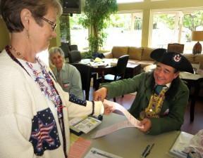 Poll worker Scott Ferguson hands a ballot to Sue Wameling as Joann Heller looks on at Scenic Hills.