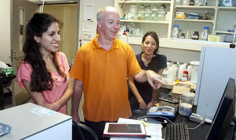 From left: senior chemistry student Farnaz Aghabarari, atmospheric chemistry professor Daniel Curtis, and senior chemistry student Maryam Ghiassee oversee the results of a sea spray aerosol test. Photo: Luis Garcia/CSUN