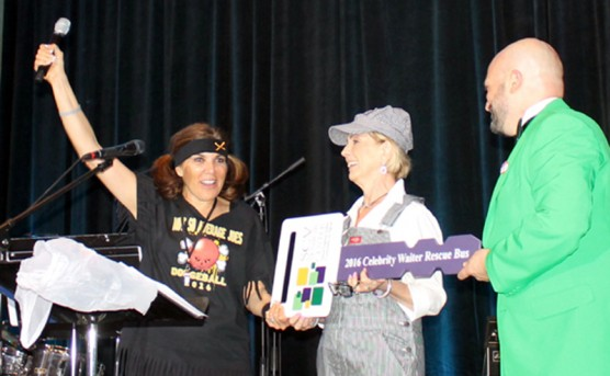 Vanessa Wilk, left and Brian Koegle, right, co-chairs of the 2016 Celebrity Waiter Dinner present a symbolic bus key to Peggy Rasmusse, center, president of the Santa Clarita Valley Committee on Aging Board of Directors, to celebrate raising enough money to fund the purchase of a new bus for the SCV Senior Center.