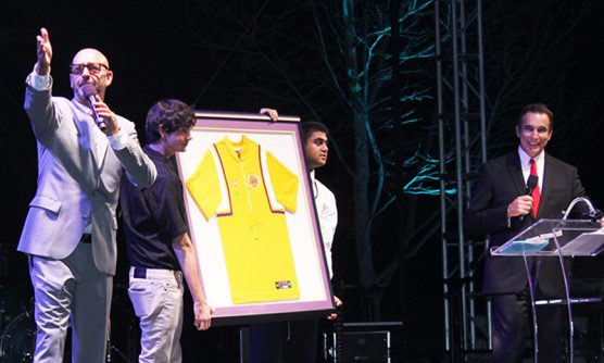Auctioneer Mark Drilling, left, works the crowd as emcee Rick Garcia, right, describes the framed autographed Kobe Bryant warm-up jersey.