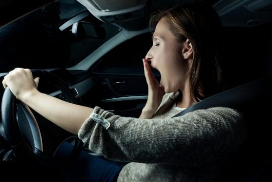 drowsy driving - Woman yawning while driving.   Photo: NHTSB