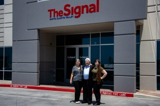 From left, Chris, Richard and Lauren Budman, the family who purchased The Signal, stand outside Signal headquarters Thursday.
