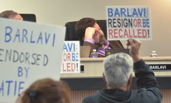 Attendees hold up protest placards against board member David Barlavi during the Saugus Union School Board meeting in Valencia on Tuesday. | Photo: Dan Watson/The Signal.