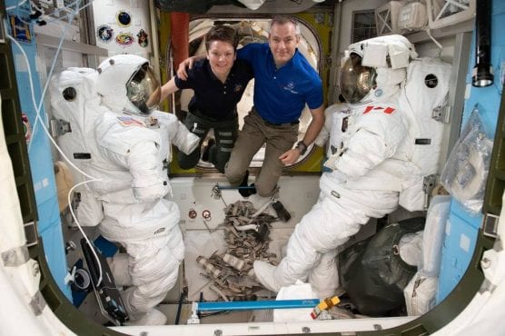 Astronauts (from left) Anne McClain and David Saint-Jacques are pictured in between a pair of spacesuits that are stowed and serviced inside the Quest airlock where U.S. spacewalks are staged. | Photo: NASA.