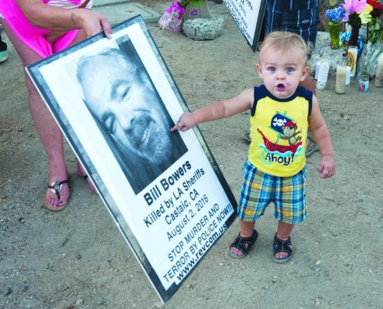 A candlelight vigil was held for Bill Bowers, who was killed in Castaic on Aug. 2, 2016. One-year-old Cameron Padilla recognizes his friend on a poster during the vigil. Signal photo.