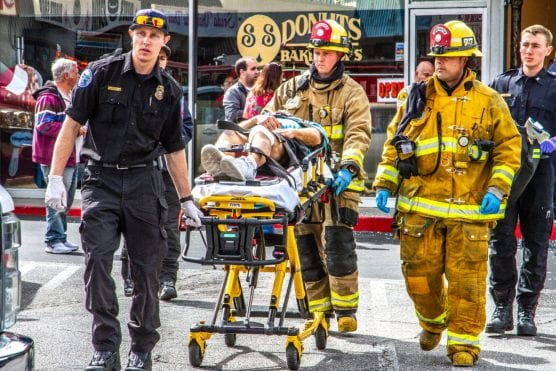 Los Angeles County Fire and American Medical Response crews work to transport a man to the hospital. The man was injured when a car slammed into a pizza shop. | Photo: Austin Dave/The Signal.