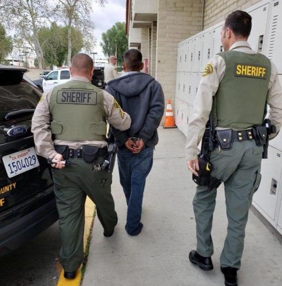 Crime Prevention Unit deputies lead David Cordova of Canyon Country to the booking desk at the Santa Clarita Valley Sheriff's Station on April 4, 2019. | LASD photo.