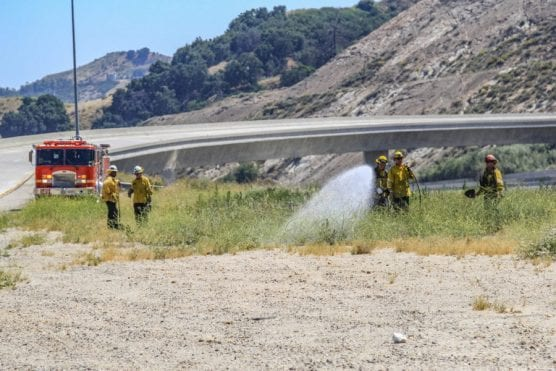 Firefighters work to put out a spot fire on the 5 and 14 freeway split Wednesday afternoon. | Photo: Lorena Mejia/The Signal.
