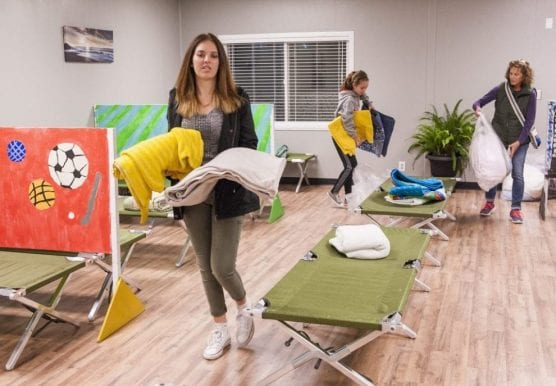 Instead of closing March 31, Bridge to Home officials are using gap funding provided by Los Angeles County Supervisor Kathryn Barger to offer services through July 31. Helping resident attendant Jayne Patafio set up the sleeping quarters in 2016 are Haley, left, and Riley Cabot, center. | Signal file photo. landlords