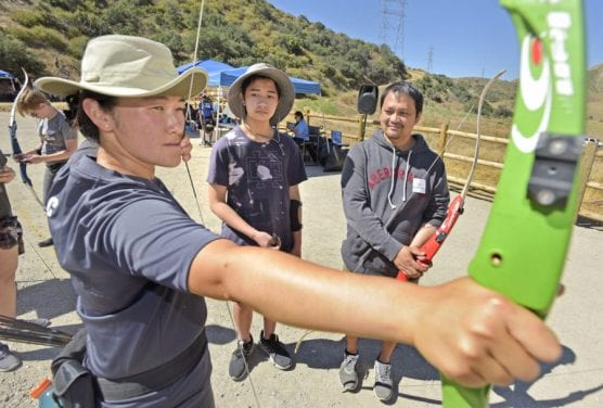 Coach Jen So, left, demonstrates how to draw and aim the bow for beginners Yuri Gumatay, 13, center, and his father Orlando of Canyon Country during the 2019 Olympic Day held at the Santa Clarita Archery Range in Canyon Country on Saturday.   Photo: Dan Watson/The Signal.