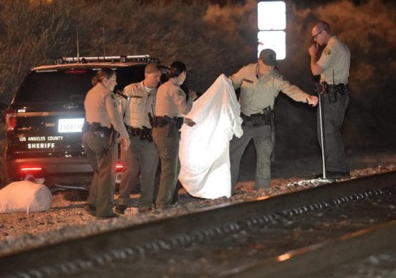 L.A. County sheriff's deputies bring out a sheet to cover the remains of a person that was apparently hit by a train near Rainbow Glen Drive and Soledad Canyon Road in Santa Clarita on Thursday night.   Photo: Dan Watson/The Signal.