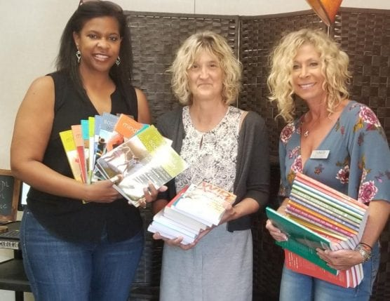 Dr. Cherise Moore (left) presents books to West Ranch Wellness Center Coordinator Nancy Phillips with WiSH Education Foundation's Amy Daniels. | Courtesy photo.