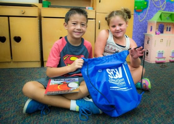 "Two children hold up a tote bag filled with books after receiving it from the Santa Clarita Valley Education Foundation ""Bag of Books"" program. Courtesy photo."