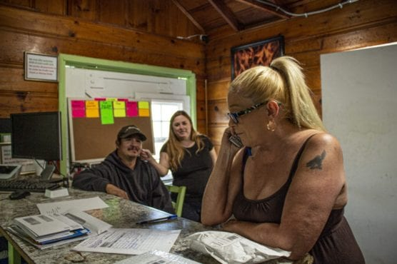 Cali-Lake RV Resort managers Serena French (foreground) and George and Michele Freeman work in the complex's office. Residents fear that they may be forced from their home and community if state and county officials pursue action to deal with what they see as overcrowding in the park. September 19, 2019. | Photo: Bobby Block/The Signal.