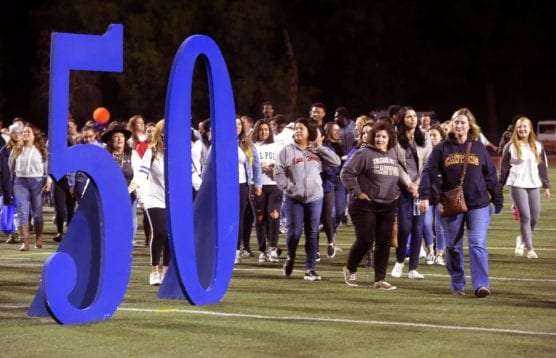 Hundreds of College of the Canyons alumni, students and faculty head to the middle of the football field for a photo during the COC 50th Anniversary celebration at College of the Canyons in Valencia on Saturday, September 28, 2019. | Photo: Dan Watson/The Signal.