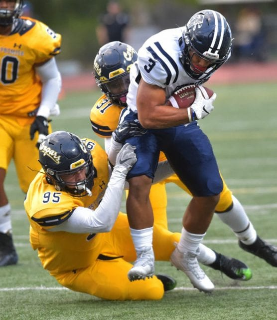 College of the Canyons' Jack Schultz (95) and Tyler Richardson (31) bring down running back Hinckley Ropati (3) of Cerritos College at COC on Saturday. | Photo: Dan Watson/The Signal.
