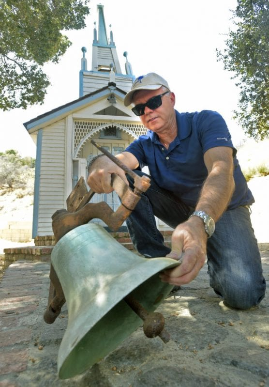 Marcelo Cairo, president of Inertia Engineers, examines the brass bell taken from the steeple atop the Ramona Chapel, behind them at Heritage Junction in Newhall on Wednesday, September 11, 2019. | Photo: Dan Watson/The Signal.