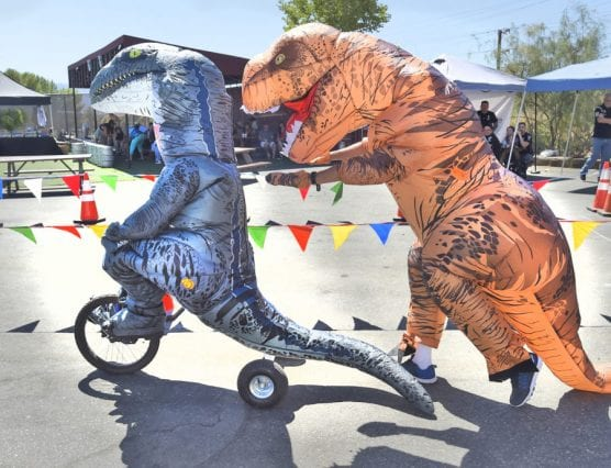 Wolf Creek Brewery teammates Joson Lester, left, riding his trike in a dinosaur suit, gets a push from Scott Wesselhoff as they compete during the Child & Family Center's 3rd annual Trike Derby held at Wolf Creek Brewery in Santa Clarita on Saturday, September 21, 2019.   Photo: Dan Watson/The Signal.