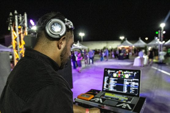 """An SOS Entertainment DJ plays music for crowds at """"Cocktails on the Roof,"""" September 6, 2019. 