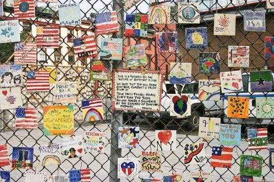 patriot day - A small monument to the victims of September 11, 2001, terrorist attacks is pictured on the fence of a car lot on Greenwich and Seventh Avenues in New York City. | Photo: DAVID ILIFF, license CC BY-SA 3.0.