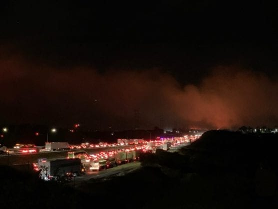 Northbound Interstate 5 near Roxford Street was at a standstill late Thursday night and early Friday morning as fires burned on both sides of the freeway. | Photo: Tammy Murga/The Signal.