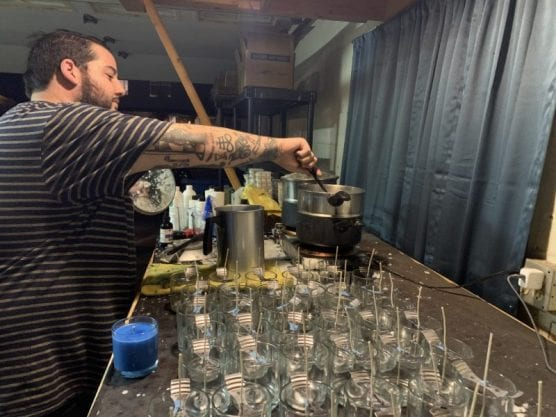 Candlemaker Tyler Coe works to create candles to be distributed. Photo courtesy of Tyler Coe.