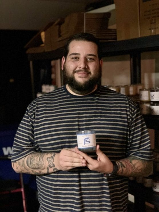 Candlemaker Tyler Coe stands with one of the finished candles. Photo courtesy of Tyler Coe.