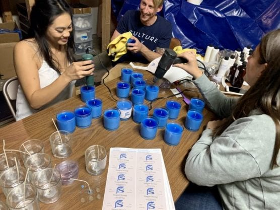 Friends of candlemaker Tyler Coe work to create the candles that will be distributed. Photo courtesy of Tyler Coe.