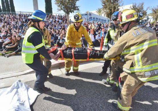 "Hundreds of Saugus High School juniors and seniors look on as first responders move the ""dead body"" of Saugus High School senior Jared Zimmerman, representing the victim in a drunk driving, head-on collision during the ""Every 15 Minutes"" event held at Saugus High School on Thursday, November 7, 2019. 