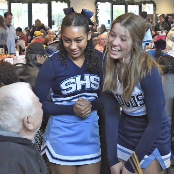 first Thanksgiving - Saugus High School cheerleaders Mikayla Pinantanida, left, and Faith Emard chat with attendees during the Senior Center Thanksgiving Gourmet Feast and Party held at the Bella Vida, Santa Clarita Valley Senior Center on Thursday, November 28, 2019.   Photo: Dan Watson / The Signal.