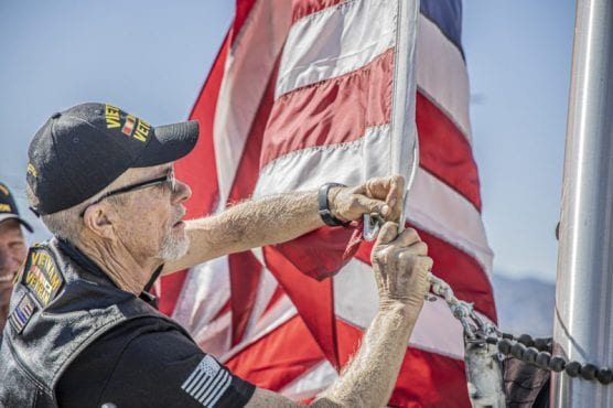 A Vietnam War veteran attaches the American Flag to the pole during the opening ceremony of the Bella Vida Senior Centers' Veterans Tribute event late Friday morning, November 8, 2019.   Photo: Bobby Block / The Signal.