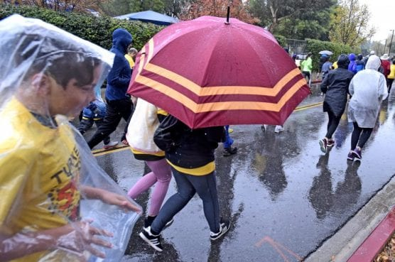 Participants carry umbrellas and wear rain gear at the take-off from the starting line of the 11th annual Thanksgiving Day Turkey Trot event at College of the Canyons on Thursday, November 28, 2019. | Photo: Dan Watson / The Signal.
