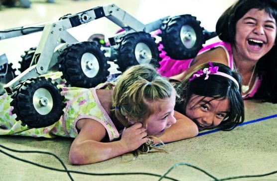 "richard cook - Santa Clarita Elementary kindergarteners, from left, Violet Abadi, Liberty French and Lizelle Gonzalez react as ""Sammy,"" the NASA Mars rover model, crawls over their backs during a science assembly presented by NASA's Jet Propulsion Laboratory for the school in Saugus in 2014. Hundreds of local residents work at the NASA-JPL facility, which also relies on parts machined in the Santa Clarita Valley, also. 