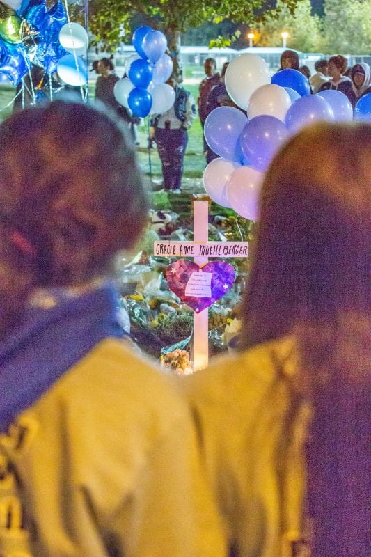 Residents stand around the memorial set up at the Central Park flag pole at the Saugus Strong Vigil Sunday night. | Photo: Cory Rubin / The Signal.