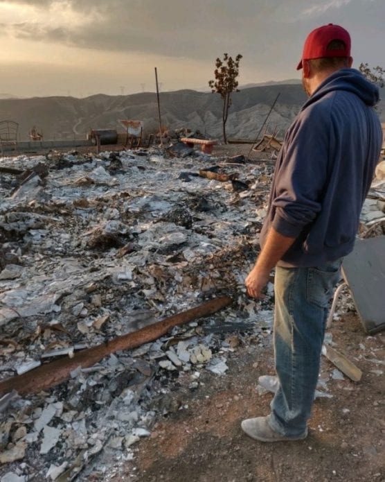 Canyon Country resident Eliseo Bugarin watches the remains of his 12-year home after the Tick Fire raged through the property.   Photo: Courtesy of the Bugarin family.