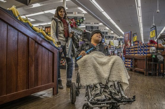 Dorota Antoniuk pushes Jose Guzman Rivera through Ralphs in Stevenson Ranch on a stroller donated by the store to assist the special education program at Pico Canyon Elementary School on December 5, 2019. | Photo: Bobby Block / The Signal.